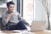 Asiatischer Mann arbeitet mit Laptop und Kaffee im Büro — Stockfoto