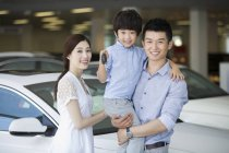 Chinese family in car dealership showroom with car keys — Stock Photo