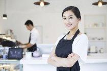 Китайская официантка, стоящая со скрещенными руками — стоковое фото