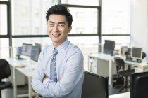 Homem de negócios chinês com os braços dobrados sorrindo no escritório — Fotografia de Stock