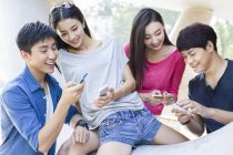 Chinese friends looking at smartphones on street — Stock Photo