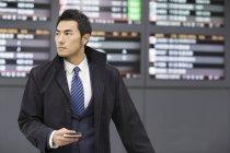 Uomo d'affari cinese in attesa in aeroporto con passaporto e smartphone — Foto stock