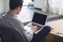 Hombre asiático trabajando con portátil en la oficina - foto de stock