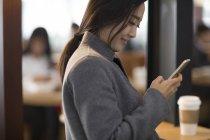 Femme asiatique utilisant un smartphone à l'aéroport — Photo de stock