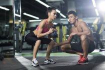 Chinese woman doing sit up with kettlebell and trainer at gym — Stock Photo