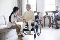 Infirmière chinoise prendre soin de la femme âgée en fauteuil roulant tandis que l'homme de lecture en arrière-plan — Photo de stock