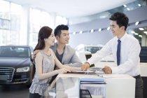 Casal chinês conversando com revendedor ao escolher o carro no showroom — Fotografia de Stock