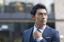 Ásia homem endireitando gravata no rua — Fotografia de Stock