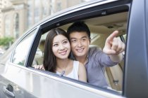 Китайская пара на заднем сиденье автомобиля, указывая в окно — стоковое фото