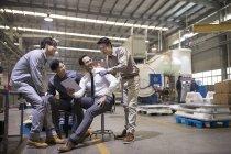 Бизнесмен и азиатские инженеры используют цифровые планшеты и разговаривают на заводе — стоковое фото