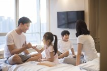 Chinese parents with children relaxing and having fun in bed — Stock Photo
