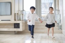 Chinese siblings holding hands and running in living room — Stock Photo