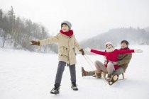 Китайський хлопчик потягнувши сани з батьками на снігу — стокове фото