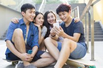 Chinese friends looking at smartphone screen together — Stock Photo
