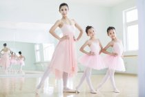 Chinese ballet instructor posing with girls in ballet studio — Stock Photo