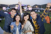 Chinese friends gesturing at music festival — Stock Photo