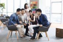 Китайський бізнес-леді показ смартфон з колегами — стокове фото
