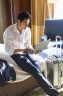 Uomo d'affari cinese che utilizza computer portatile sul letto nella camera d'albergo — Foto stock