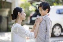 Cinese madre abbottonatura figlio camicia su strada — Foto stock
