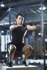 Homem chinês fazendo caixa de salto no ginásio crossfit — Fotografia de Stock