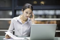 Tired Chinese businesswoman working late in office — Stock Photo