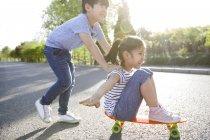 Китайский мальчик, толкая девушка на скейтборде — стоковое фото