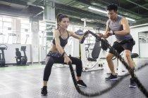 Asiatische Frau trainieren im Fitnesscenter mit trainer — Stockfoto