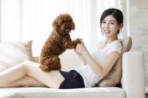Молодая китаянка играет с пуделем на диване — стоковое фото