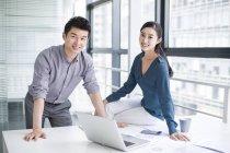 Chinesische Kollegen sitzen mit Laptop im Büro — Stockfoto