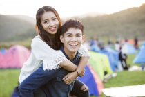 Chinese couple riding piggyback at festival camping — Stock Photo