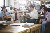 Compañeros de trabajo hablar de trabajan en oficina - foto de stock