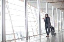 Азиатка тащит багаж в вестибюле аэропорта — стоковое фото