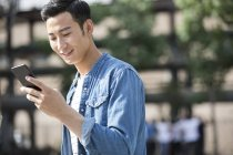 Chinois utilisant un smartphone en ville — Photo de stock