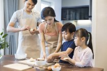 Chinese family with siblings baking together in kitchen — Stock Photo