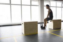 Asian man sitting at gym — Stock Photo