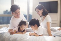 Chinese parents and children reading book in bed — Stock Photo