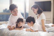 Padres chinos y niños de la lectura del libro en la cama - foto de stock