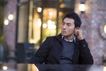 Asiatique homme assis à la table sur la rue urbaine — Photo de stock