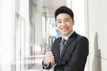 Portrait of chinese businessman doing thumbs up — Stock Photo