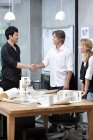 Male architects shaking hands in office — Stock Photo