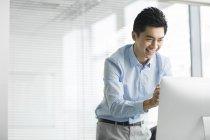 Homme d'affaires chinois souriant et à l'aide d'ordinateur de bureau — Photo de stock