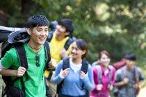 Gruppe von chinesischen Rucksacktouristen Wandern im Wald — Stockfoto