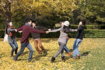 Chinese young adults running in circle in park in autumn — Stock Photo