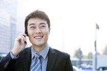Китайский бизнесмен разговаривает по телефону на улице — стоковое фото