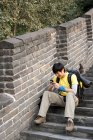 Chinese tourist using smartphone on Great Wall steps — Stock Photo