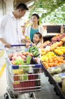 Chinese girl with parents buying fruits in supermarket — Stock Photo