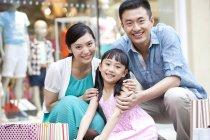 Китайские родители и дочь, позируя с Сумки для покупок в торговом центре — стоковое фото