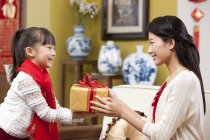 Little girl presenting Chinese New Year gift to mother — Stock Photo