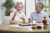 Senior chinesisches Paar frühstückt mit Süßigkeiten — Stockfoto