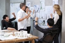 Team of architects looking at wall and cheering in office — Stock Photo